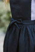 Woman wearing black linen apron, up close image of a details