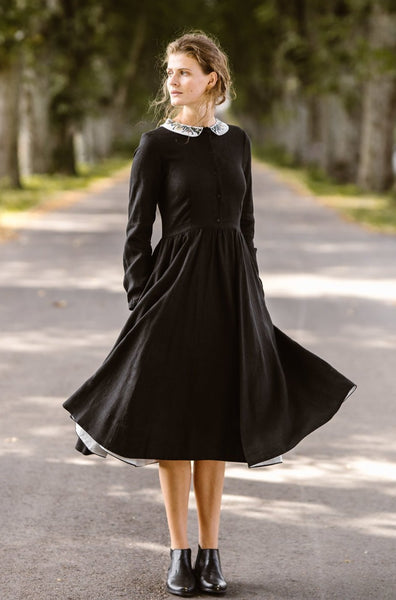 Woman wearing black classic dress with long sleeves and embroidered meadow peter pan collar, picture from the front
