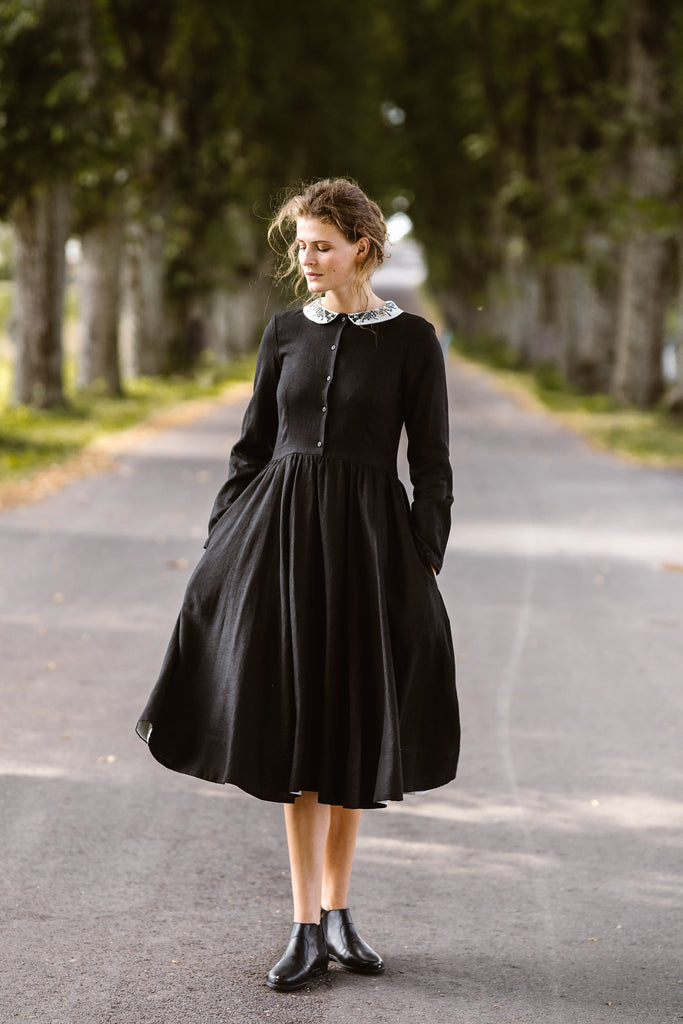 Woman wearing black classic dress with long sleeves and embroidered meadow peter pan collar, image from the front