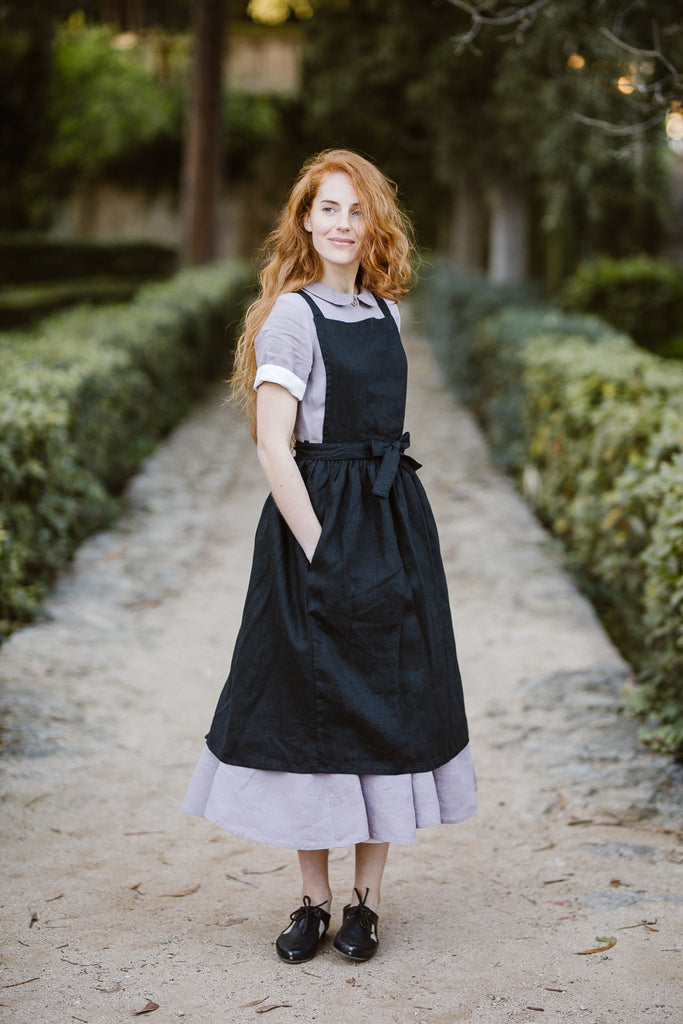 Woman wearing black linen apron, image from the front