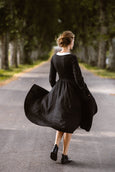 Woman wearing black classic dress with long sleeves and embroidered meadow peter pan collar, image from the back