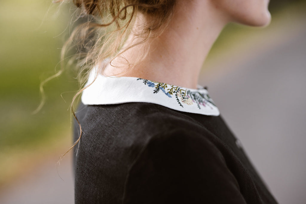 Woman wearing black dress with long sleeves and embroidered meadow peter pan collar, image of a collar from the side