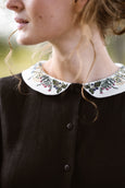 Woman wearing black classic dress with long sleeves and embroidered meadow peter pan collar, up close image of a collar