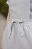 Woman wearing natural linen apron, up close image from the front