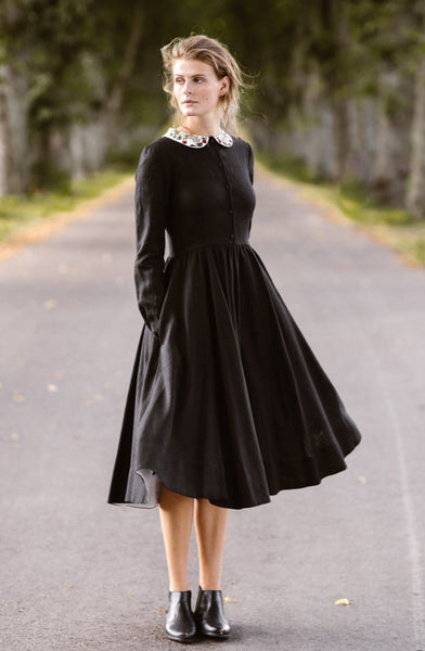 Woman wearing black classic dress with long sleeves and embroidered garden peter pan collar, picture from the front.