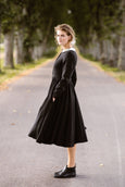 Woman wearing black classic dress with long sleeves and embroidered garden peter pan collar, image from the side
