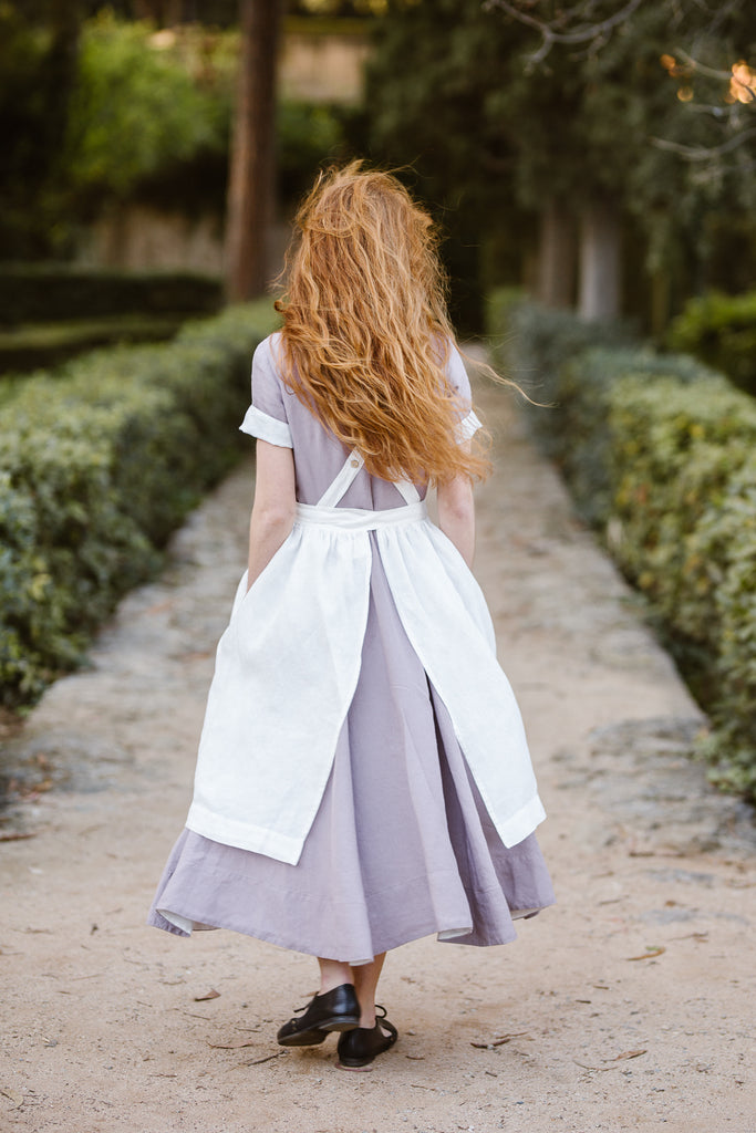 Woman wearing white linen apron, image from the back