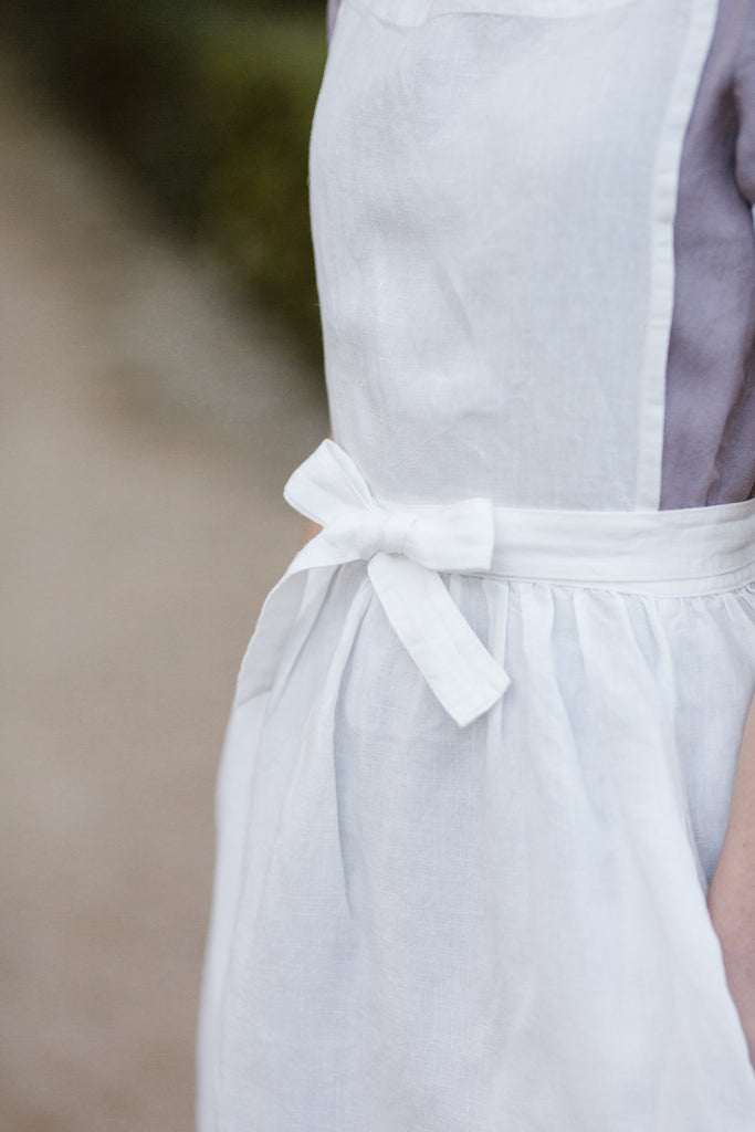 Woman wearing white linen apron, up close image of a details