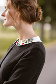 Woman wearing black classic dress with long sleeves and embroidered garden peter pan collar, up close image from the side