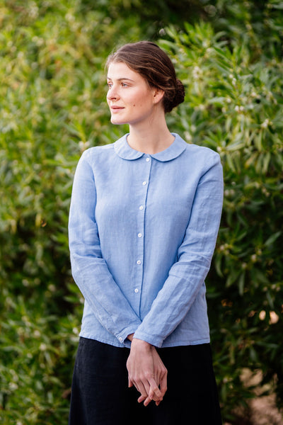 Woman wearing light blue linen shirt with white buttons