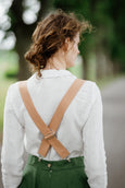 Model wearing beige color linen suspenders with adjustable clip-end, up-close picture from the back.