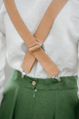 Woman wearing beige color linen suspenders with adjustable clip-end, up-close picture from the back.