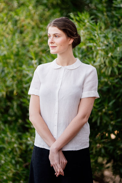Woman wearing white linen shirt with short sleeves and peter pan collar