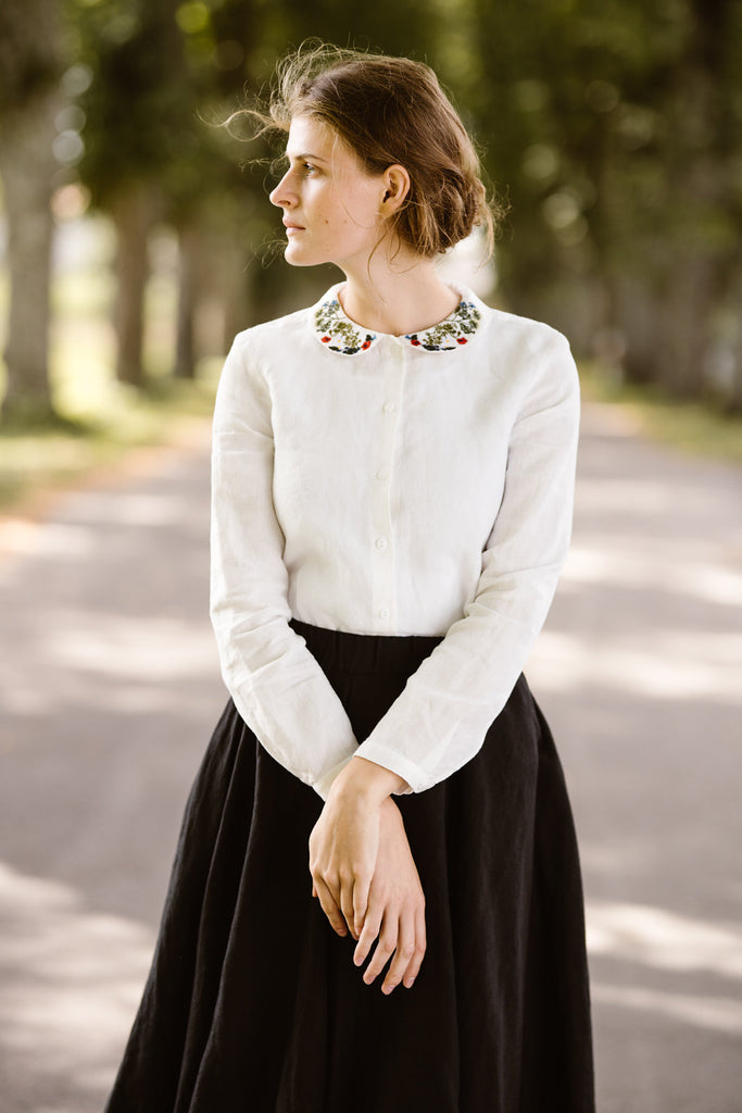 Woman wearing white minimalist linen shirt with long sleeves and garden embroidery collar, image from the front