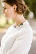Woman wearing white minimalist linen shirt with long sleeves and garden embroidery collar, up close image of a collar