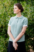 Woman wearing linen shirt in green mint color with short rolled up sleeves,peter pan collar and buttons down the front