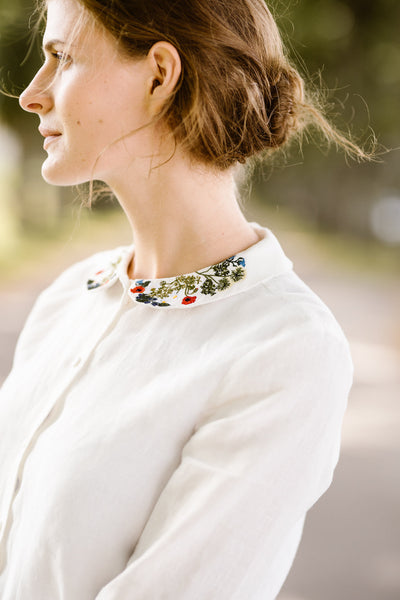 Woman wearing white minimalist linen shirt with long sleeves and garden embroidery collar, up close image from the side
