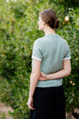Picture from the back: woman wearing light green mint linen shirt with short sleeves