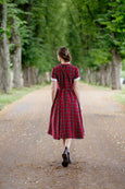 Woman in a red tartan dress with short sleeves, picture from the back