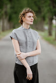 Woman wearing grey color pleated detail shirt with short sleeves, image from the front