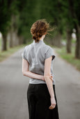 Woman wearing grey color pleated detail shirt with short sleeves, image from the back