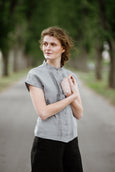 Woman wearing grey color pleated detail shirt with short sleeves, picture from the front
