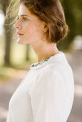 Woman wearing white minimalist linen shirt with long sleeves and meadow embroidery collar, up close image from the side