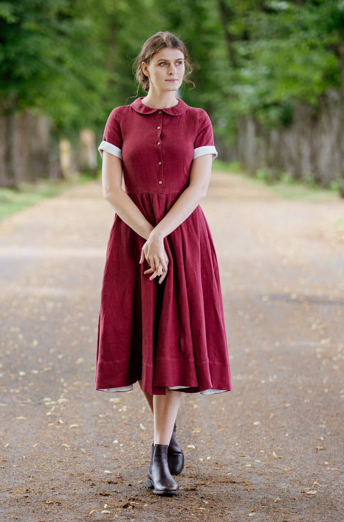 Woman wearing linen marsala red dress.