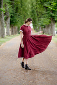 Woman wearing classic linen dress in burgundy color