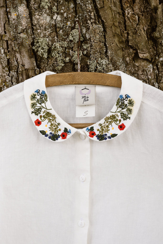 White minimalist linen shirt with long sleeves and garden embroidery collar, up close image from the front