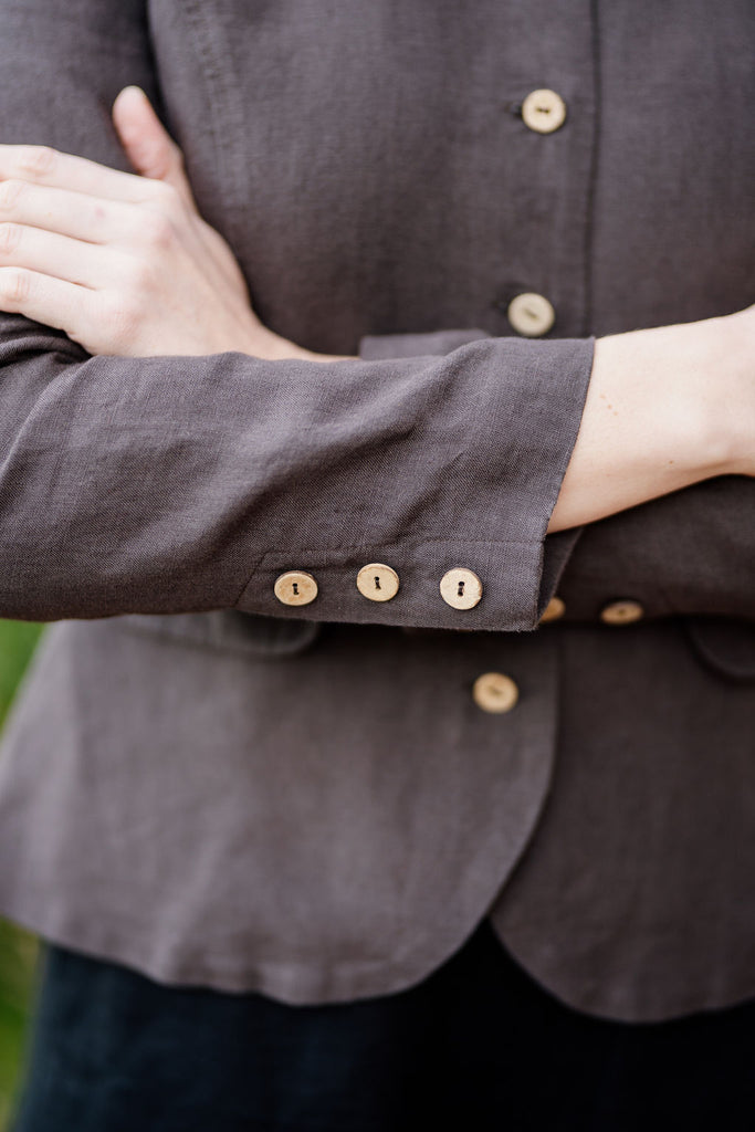 Up close detail of dark brown linen jacket and natural buttons