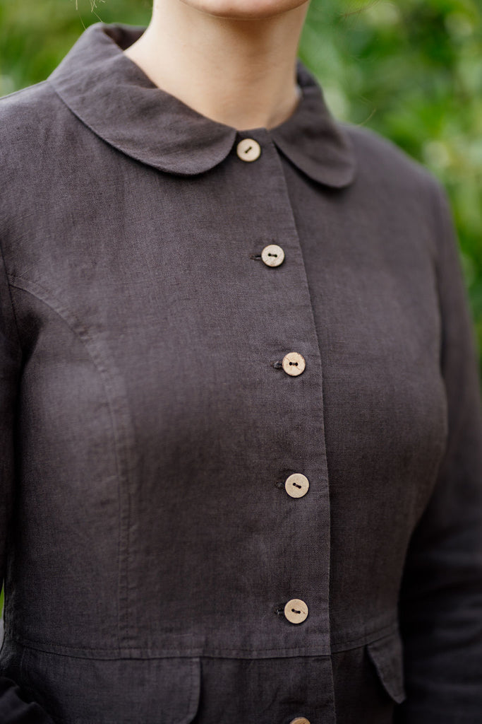 Up close picture of linen jacket in dark brown color with button detail and peter pan collar