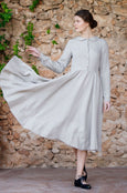 Classic dress in natural linen color with buttoned up front detail, long sleeves and full a-line skirt