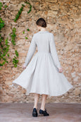 Picture from the back: woman walking in natural linen dress with long sleeves