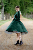 Model wearing emerald green linen dress with long sleeves