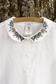 White minimalist linen shirt with long sleeves and meadow embroidery collar, up close image from the front
