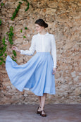 Woman wearing midi linen full a-line skirt in light blue color