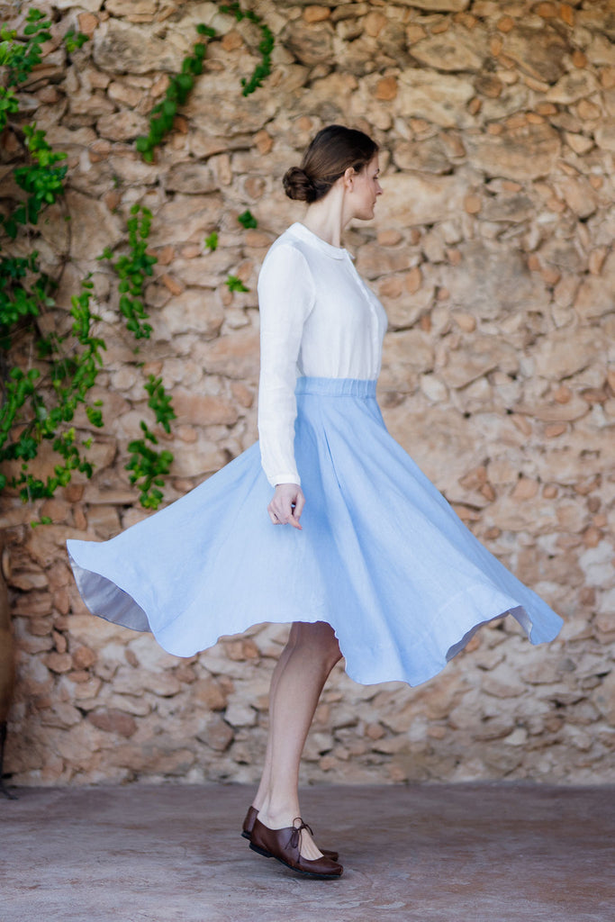 Woman turning in full a-line linen skirt in light blue color