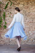 Woman walking in a midi light blue skirt with pockets