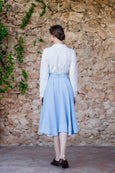Photo from the back: woman walking in light blue linen skirt