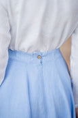 Picture of the button and a zipper detail on a light blue linen skirt