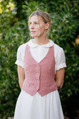 Woman wearing white linen dress and pink waistcoat with button detail