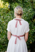 Picture from the back: woman wearing white linen dress and pink vest