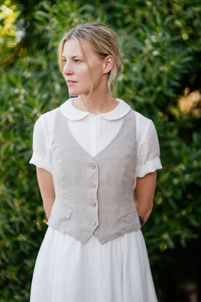 Woman wearing white linen dress and natural linen waistcoat
