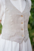 Button detail on a linen vest in natural sand color