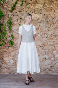 Woman in white linen dress and natural sand color vest