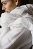 Woman wearing white wedding shawl, up close image from the side