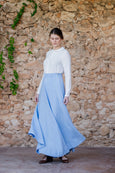 Woman wearing long linen skirt in sky blue and white shirt