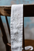 White embroidered ribbon belt, up close image from the front