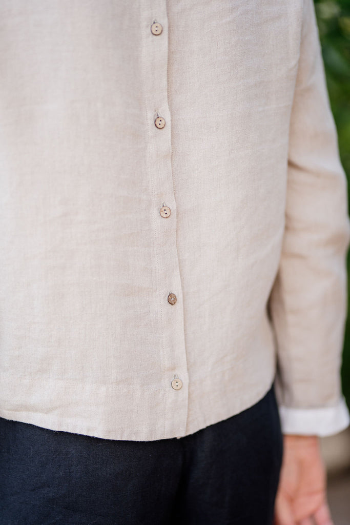 up close picture of the back of a linen women shirt, buttons along the spine, long sleeves with white roll up